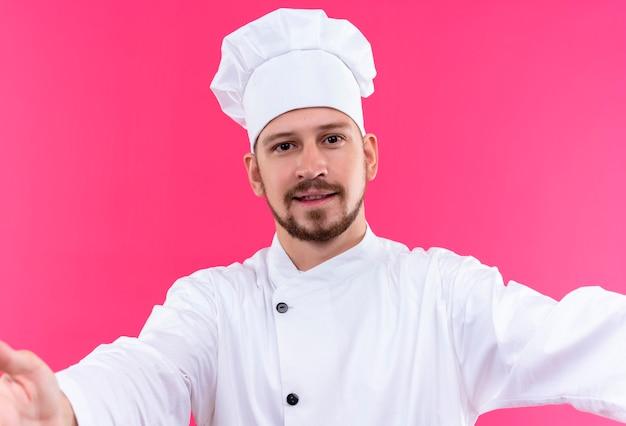 プロの男性シェフが白い制服を着て調理し、ピンクの背景の上に立って笑顔の歓迎のジェスチャーを作る広い手を開く帽子を調理します。