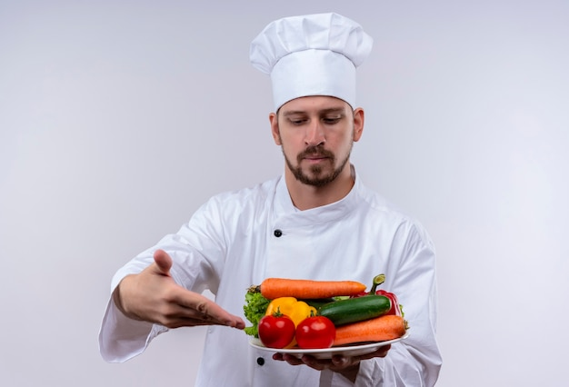 白い制服を着たプロの男性シェフが調理し、白い背景の上に自信を持って立っている野菜のプレートを提示する帽子を調理します。