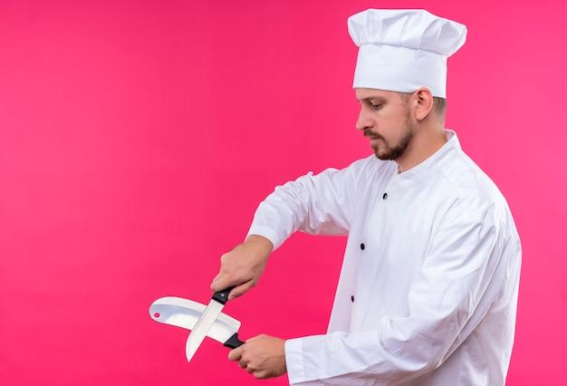 Профессиональный шеф-повар-мужчина в белой униформе и поварская шляпа точит ножи, стоя на розовом фоне