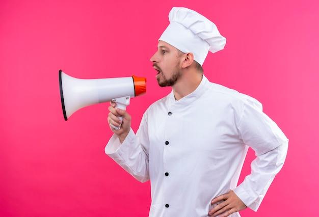 白い制服を着たプロの男性シェフが調理し、ピンク色の背景の上に立ってメガホンに叫んで帽子を調理します。