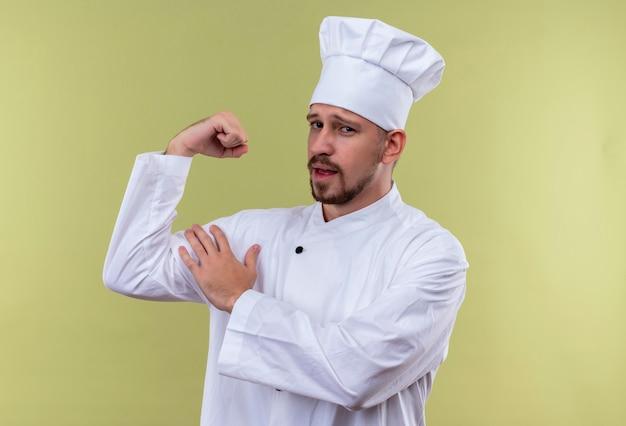 プロの男性シェフが白い制服を着て調理し、上腕二頭筋がグリーの背景に自己満足と誇りを持って立っているように見えることを示す