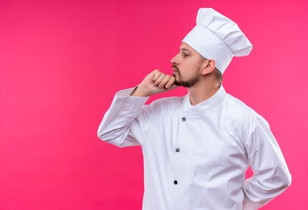 プロの男性シェフが白い制服を着て調理し、ピンクの背景を考えてあごに手で横に立って帽子を調理します。