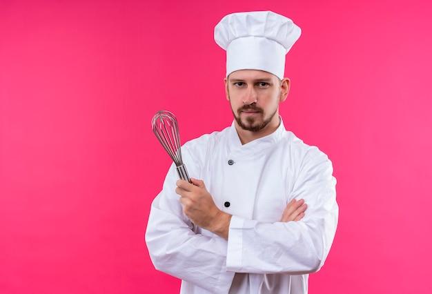 プロの男性シェフが白い制服を着て調理し、腕を組んで帽子をかぶってピンクの背景に真剣な表情で見ている泡立て器を保持