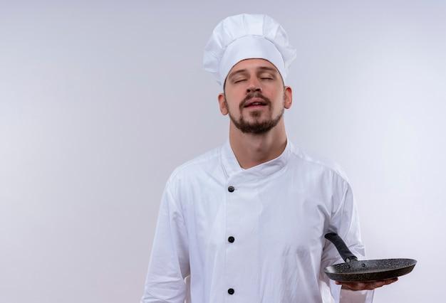 白い制服でプロの男性シェフが調理し、白い背景の上にフライパンをかざして目を閉じて立っている帽子を調理します。