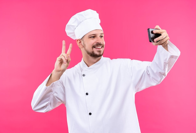 プロの男性シェフが白い制服を着て調理し、ピンクの背景の上に立って笑みを浮かべて勝利のサインを示す彼のスマートフォンを使用してselfieを取って帽子を調理します