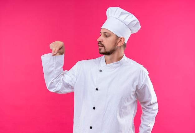 Chef maschio professionista cuoco in uniforme bianca e cappello da cuoco gesticolando con la mano guardando fiducioso in piedi su sfondo rosa