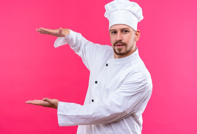 Professional male chef cook in white uniform and cook hat gesturing with hands showing size, measure symbol over pink background