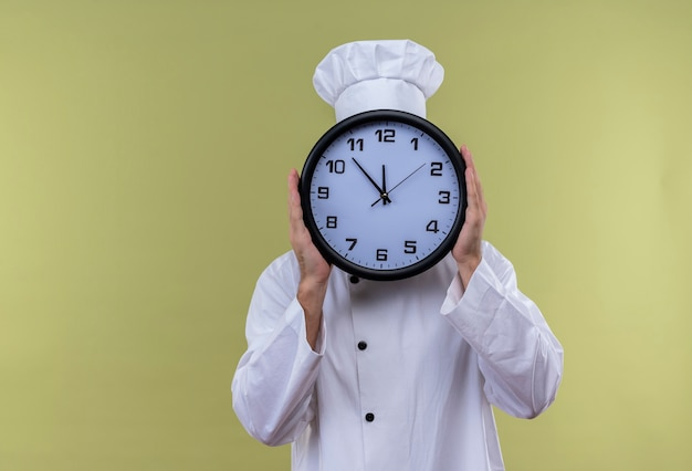 Chef maschio professionista cuoco in uniforme bianca e cappello da cuoco che nasconde il viso dietro il grande orologio in piedi su sfondo verde