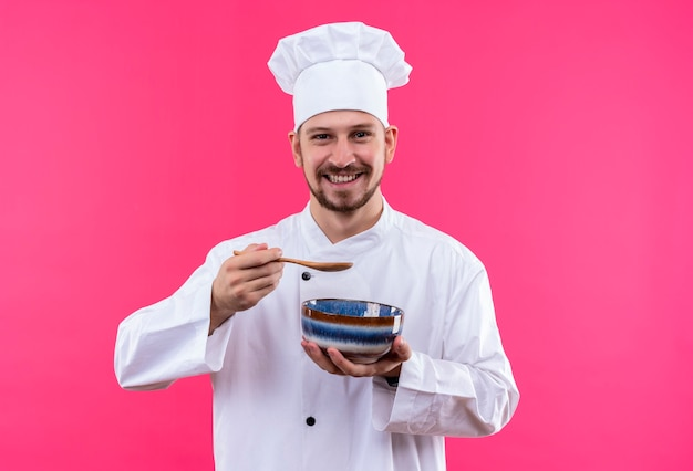 Professional male chef cook in white uniform and cook hat holding a bowl tasting soup with spoon smiling standing over pink background