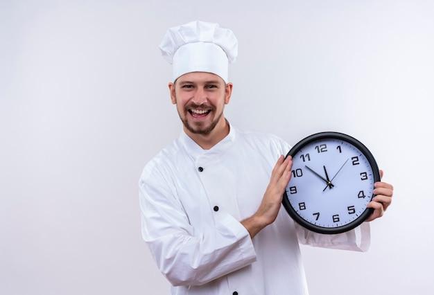 Chef maschio professionista cuoco in uniforme bianca e cappello da cuoco in possesso di un orologio guardando sorridente allegramente in piedi su sfondo bianco
