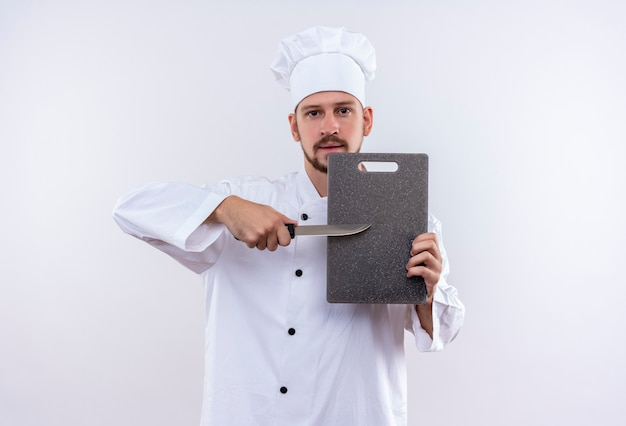 Professional male chef cook in white uniform and cook hat holding cutting board and knife looking confident standing over white background