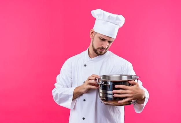 Chef maschio professionista cuoco in uniforme bianca e cappello da cuoco che tiene una padella vuota guardandolo con espressione triste sul viso infelice in piedi su sfondo rosa