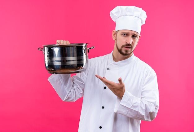 Chef maschio professionista cuoco in uniforme bianca e cappello da cuoco che tiene una padella vuota che punta ad esso con il braccio della sua mano guardando da parte con espressione scettica sul viso in piedi su sfondo rosa