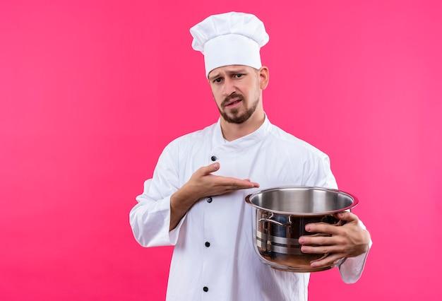 Chef maschio professionista cuoco in uniforme bianca e cappello da cuoco che tiene una pentola vuota che punta ad esso con il braccio della sua mano che guarda l'obbiettivo con espressione scettica sul viso in piedi su sfondo rosa