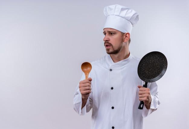 Cuoco unico maschio professionista cuoco in uniforme bianca e cappello da cuoco che tiene padella e cucchiaio di legno che sembra preoccupato in piedi su sfondo bianco