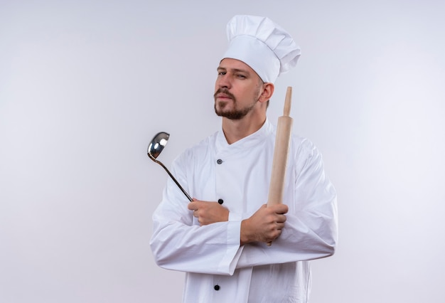 Professional male chef cook in white uniform and cook hat holding ladle and rolling pin looking at camera with suspicious expression standing over white background