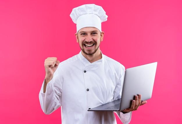 Chef maschio professionista cuoco in uniforme bianca e cappello da cuoco che tiene il computer portatile che guarda l'obbiettivo sorridente allegro alzando il pugno rallegrandosi del suo successo in piedi su sfondo rosa