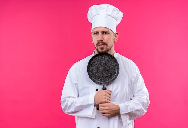 Chef maschio professionista cuoco in uniforme bianca e cappello da cuoco che tiene una padella alooking da parte con espressione scettica sul viso in piedi su sfondo rosa