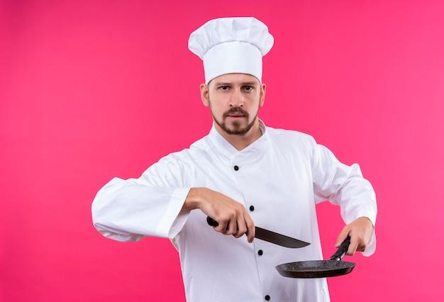 Chef maschio professionista cuoco in uniforme bianca e cappello da cuoco che tiene una padella e un coltello che guarda l'obbiettivo con espressione fiduciosa in piedi su sfondo rosa