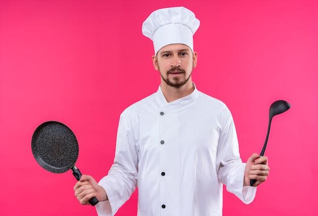 Chef maschio professionista cuoco in uniforme bianca e cappello da cuoco che tiene padella e mestolo che guarda l'obbiettivo con un sorriso fiducioso in piedi su sfondo rosa