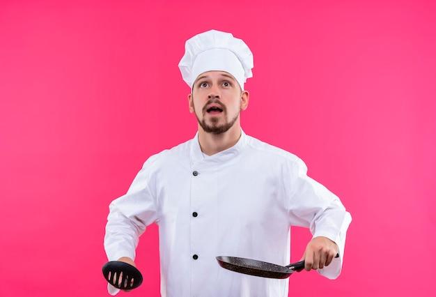 Chef maschio professionista cuoco in uniforme bianca e cappello da cuoco che tiene una pentola e un mestolo che osserva in su incuriosito in piedi su sfondo rosa