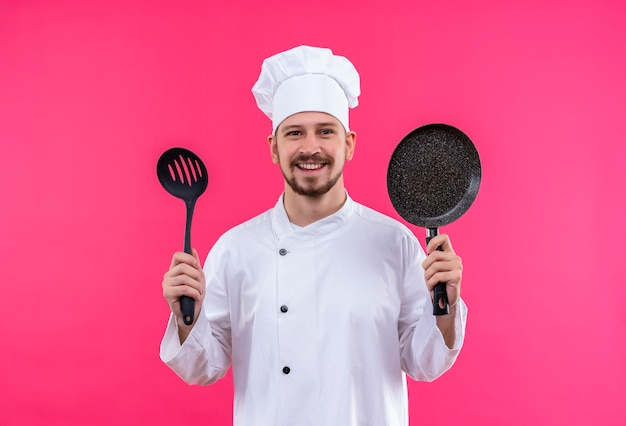 Professional male chef cook in white uniform and cook hat holding a pan and ladle smiling cheerfully looking at camera standing over pink background