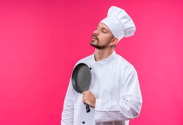 Professional male chef cook in white uniform and cook hat holding a pan looking aside self-satisfied and proud standing over pink background