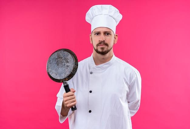 Chef maschio professionista cuoco in uniforme bianca e cappello da cuoco che tiene una padella che guarda l'obbiettivo con l'espressione fiduciosa sul viso in piedi su sfondo rosa