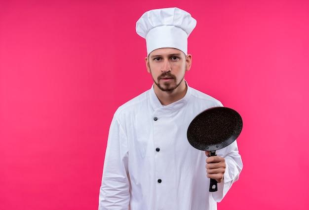 Chef maschio professionista cuoco in uniforme bianca e cappello da cuoco che tiene una padella che guarda l'obbiettivo con espressione seria in piedi su sfondo rosa