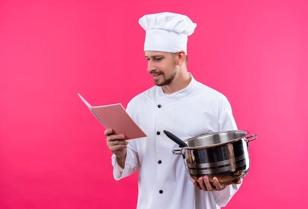 Chef maschio professionista cuoco in uniforme bianca e cappello da cuoco che tiene una padella e un taccuino guardandolo sorridente in piedi su sfondo rosa