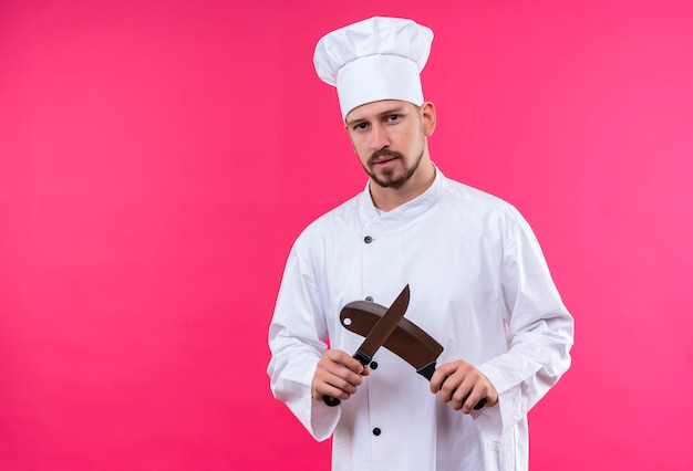 Professional male chef cook in white uniform and cook hat holding sharp knifes looking at camera with serious face standing over pink background