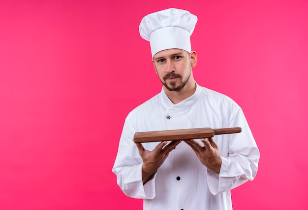 Professional male chef cook in white uniform and cook hat holding wooden cutting board looking confident standing over pink background