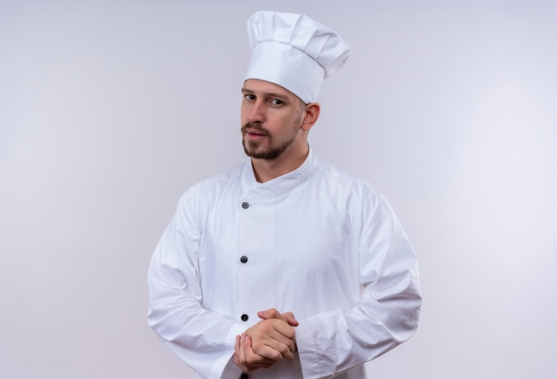 Professional male chef cook in white uniform and cook hat looking at camera with confidentserious expression rubbing hands waiting for something standing over white background