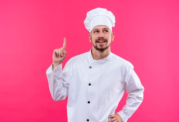 Professional male chef cook in white uniform and cook hat looking up pointing with finger reminding himself no to forget important thing standing over pink background