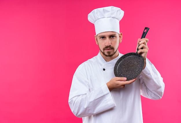 Chef maschio professionista cuoco in uniforme bianca e cappello da cuoco che presenta una padella che guarda l'obbiettivo con espressione seria e fiduciosa sul viso in piedi su sfondo rosa