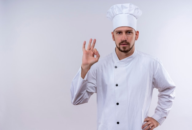 Professional male chef cook in white uniform and cook hat showingok sign looking confident standing over white background