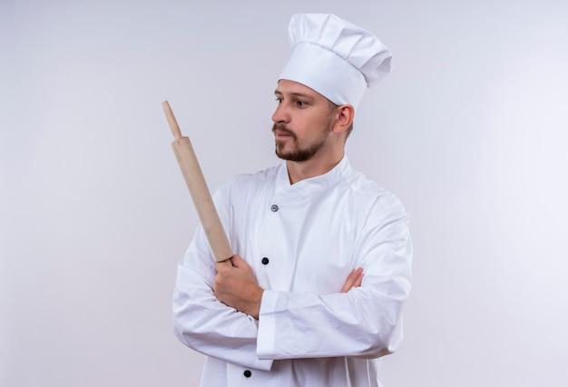 Chef maschio professionista cuoco in uniforme bianca e cappello da cuoco in piedi con le braccia incrociate tenendo il mattarello che guarda da parte con espressione fiduciosa su sfondo bianco