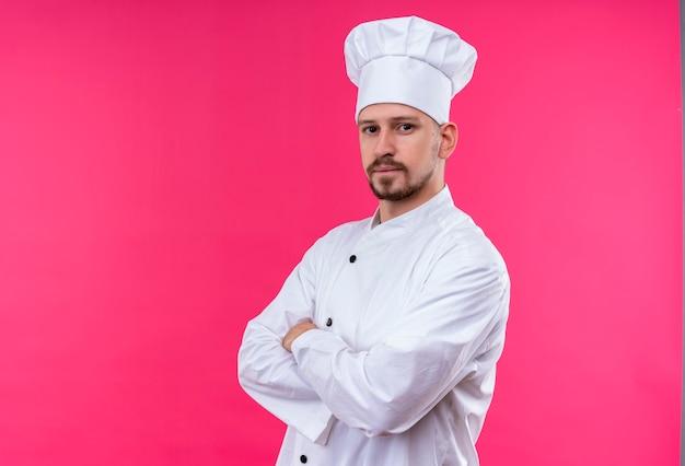 Chef maschio professionista cuoco in uniforme bianca e cappello da cuoco in piedi con le braccia incrociate guardando fiducioso su sfondo rosa