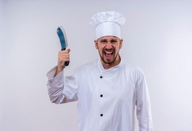 Chef maschio professionista cuoco in uniforme bianca e cappello da cuoco che oscilla un coltello affilato con espressione aggressiva in piedi su sfondo bianco