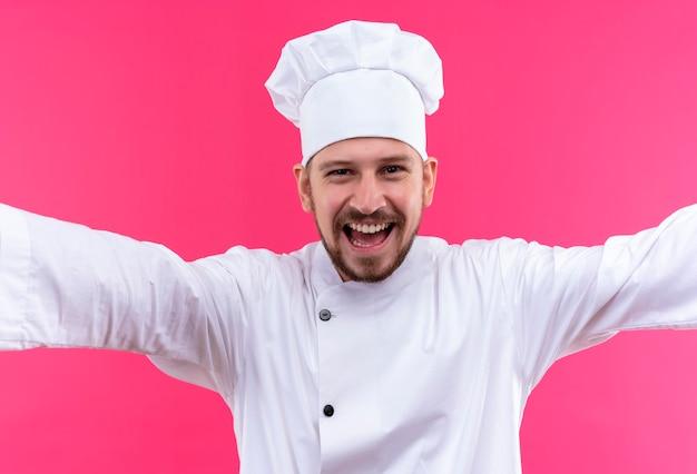Chef maschio professionista cuoco in uniforme bianca e cappello da cuoco con ampia apertura mani che fa gesto di benvenuto sorridente allegramente in piedi su sfondo rosa