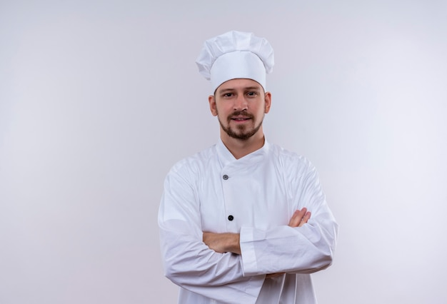 Professional male chef cook in white uniform and cook hat with arms crossed smiling confident standing over white background