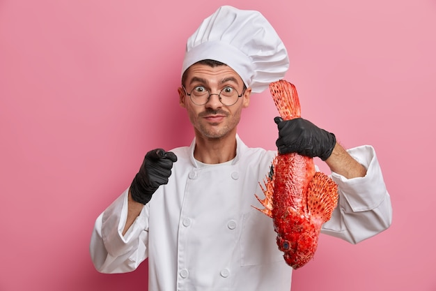 Professional male chef holds big red uncooked fish, suggests to cook delicious meal for you