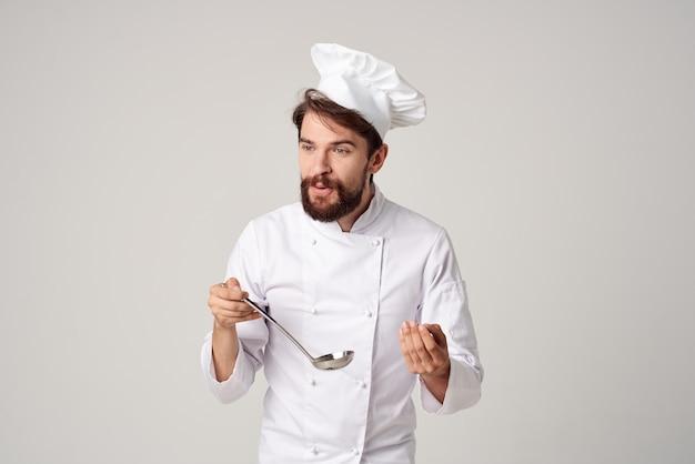 Профессиональный шеф-повар-мужчина с черпаком в руках, работающий в ресторане