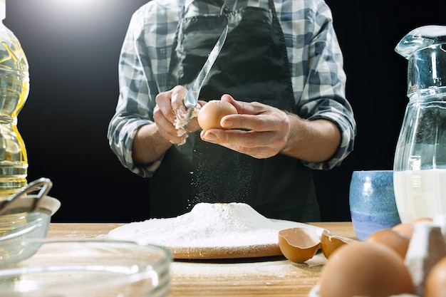 Professional male cook sprinkles dough with flour, preapares or bakes bread or pasta at kitchen table