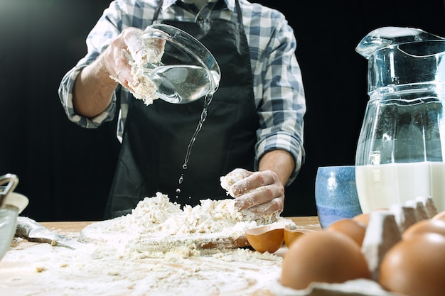 プロの男性料理人は、小麦粉、preaparesまたは焼きたてのパンやパスタを台所のテーブルで生地に振りかける、汚いユニフォーム、黒いチョークの背景に分離されています。ベーキングコンセプト