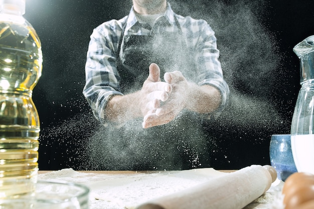 Professional male cook sprinkles dough with flour