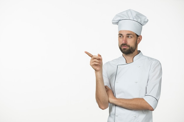 Professional male cook standing against white backdrop pointing at something