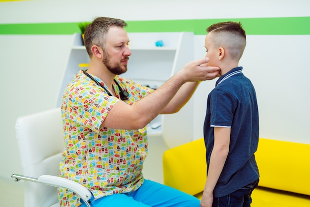 プロの男性医師は、医療センターで小さな男の子のリンパ節をチェックします。小児科医は幼稚な喉を調べています。医療。