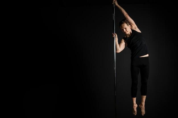 Maschio professionista facendo una pole dance