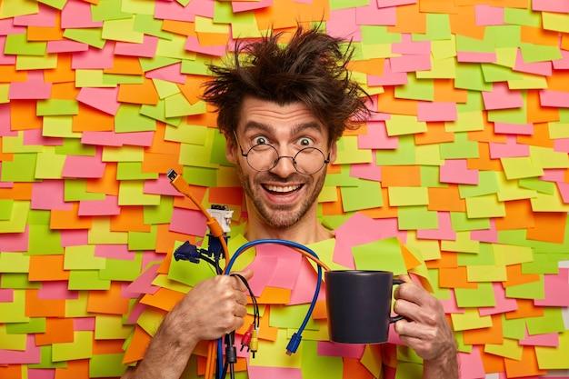 プロの男性エンジニアがケーブルを持ち、コンピューターを接続する準備ができて、最新のテクノロジーを手伝ってくれ、コーヒーを飲み、前向きに笑い、色付きのステッカーで紙の壁から頭を突き出します